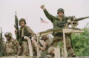 FILE - In a Dec. 10, 1992 file photo, a U.S. Marine gives the thumbs up as a truck load of troops arrive at the reopened U.S. Embassy in Mogadishu, Somalia. According to the U.S. Africa Command on Friday April 14, 2017, the U.S. military is sending dozens of regular troops to Somalia to train Somali soldiers in the largest such deployment to the Horn of Africa country in roughly two decades. (Denis Pauqin, File/Associated Press)