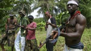 FILE- Militants stand guard at Okorota, near Port Harcourt, Nigeria. Nigeria's government resumed paying stipends to former militants in August 2016, even as security forces reported killing scores of fighters disrupting petroleum production in the oil-rich Niger Delta.