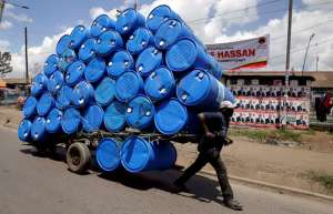 FILE PHOTO: A porter transports a cart loaded with empty plastic drums to a recycling dealer in the outskirts of Kenya's capital of Nairobi April 26, 2017. REUTERS/Thomas Mukoya/File Photo