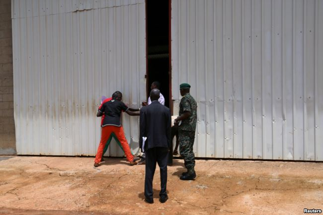 Soldiers pull open the doors to a warehouse inside former Gambian President Yahya Jammeh's personal estate in Kanilai, Gambia, July 1, 2017.