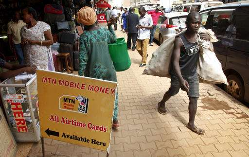 In this photo taken Thursday, Sept. 29, 2016, pedestrians walk past a mobile money point in Kampala, Uganda. Mobile money has become a way of life for millions of Africans who use their phones to pay utility bills, settle loans and even bail out friends in distress. (AP Photo/Stephen Wandera)