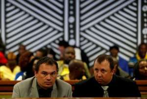 FILE PHOTO: Farmers Willem Oosthuizen and Theo Martins look on during a court appearance in Delmas, Mpumalanga province, South Africa, July 31, 2017. REUTERS/Siphiwe Sibeko/File Photo
