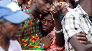 A woman is comforted after learning she has lost her son