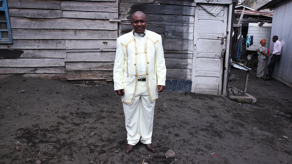 """Theobold Kawa, a 55-year-old pastor, stands outside of AEPL Makedonia church in Goma. He bought his suit in Uganda. """"I'm dressing up like this because of the Glory of God,"""" he says. """"A servant of God shouldn't look dirty."""" Shayla Harris"""