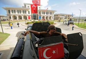 A member of the Turkish security forces sits inside an armored vehicle outside the newly opened Turkish embassy in Mogadishu on June 3, 2016. After increasing diplomatic and humanitarian support for Somalia, Turkey established a military training camp in the country. MOHAMED ABDIWAHAB/AFP/GETTY IMAGES