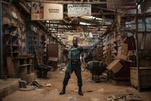 A security guard poses in an empty alleyway in Ogbaru Market in May 2017, during a shutdown in commemoration of the 50th anniversary of the Nigerian Civil War (AFP Photo/STEFAN HEUNIS )