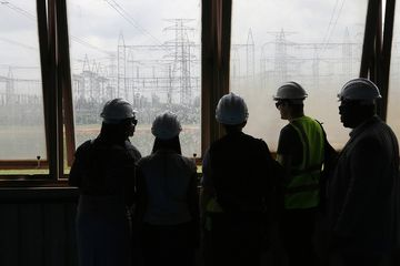 Visitors look at electricity pylons carrying power lines at the newly renovated energy generation plant, operated by Egbin Power Plc, in Lagos, Nigeria, on Wednesday, Aug. 26, 2015. While Nigeria was the world's fourth-biggest exporter of liquefied natural gas in 2012, it's struggling to meet local demand for the fuel used by plants that generate at least 70 percent of the country's electricity needs. Photographer: George Osodi/Bloomberg