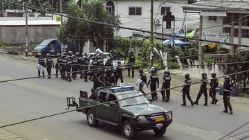 Cameroon police officials with riot equipment patrol along a street in the administrative quarter of Buea some 60kms west of Douala on October 1, 2017. A young man from Cameroon's English-speaking region was shot dead by security forces in the city of Kumba on the eve of an expected symbolic declaration of independence by anglophone separatists, medical and security forces told AFP. / AFP PHOTO / STRINGER (Photo credit should read STRINGER/AFP/Getty Images)