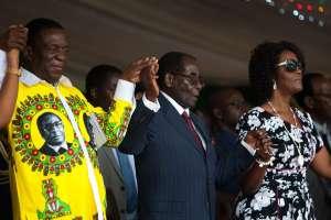 Zimbabwe's President Robert Mugabe sits with his wife Grace Mugabe and Vice President Emmerson Mnangagwa
