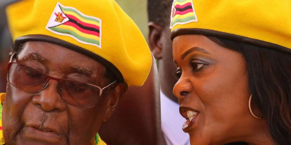 FILE PHOTO: President Robert Mugabe listens to his wife Grace Mugabe at a rally of his ruling ZANU(PF) party in Harare, Zimbabwe, November 8, 2017.REUTERS/Philimon Bulawayo/File Photo