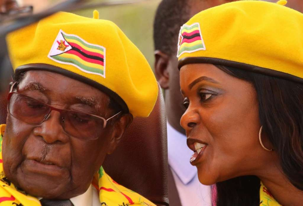 FILE PHOTO: President Robert Mugabe listens to his wife Grace Mugabe at a rally of his ruling ZANU(PF) party in Harare, Zimbabwe, November 8, 2017. REUTERS/Philimon Bulawayo/File Photo