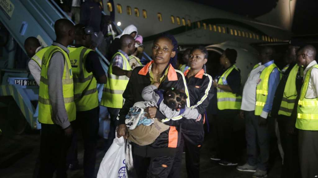 Nigeria returnees from Libya  disembark  from Libya  disembark from a plane upon arrival at the Murtala Muhammed International Airport Lagos Nigeria Tuesday, Dec. 5, 2017. The African Union has agreed to evacuate more than 15,000 African migrants from Libya by the end of the year in a scaled-up evacuation process along with member states who have expressed outrage since video footage aired weeks ago of migrants being auctioned off as slaves.  (AP Photo/Sunday Alamba)