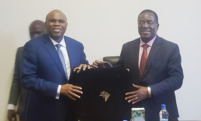 Afreximbank President Dr. Benedict Oramah (left) presenting a gift to Acting President Emmerson