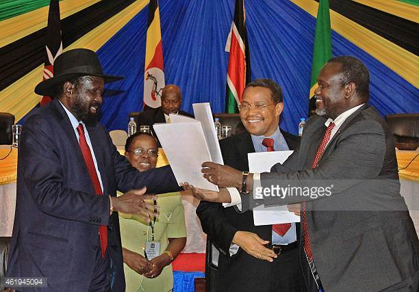 File Picture .South Sudan's President Salva Kiir exchanges signed documents with South Sudanese rebel leader Riek Machar  following previous peace accords which collapsed spectacularly