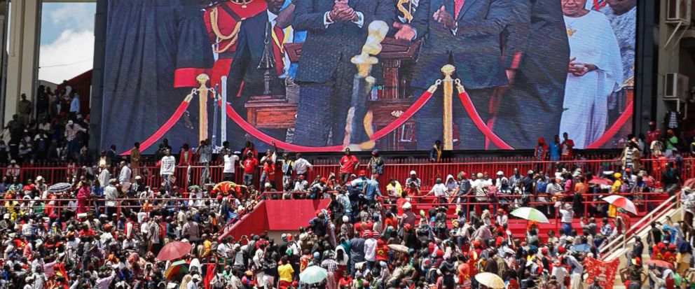 "FILE - In this Tuesday, Nov. 28, 2017 file photo, the crowd watch as Kenyan President Uhuru Kenyatta, center, and Deputy President William Ruto, center right, appear on a video screen at his inauguration ceremony at Kasarani stadium in Nairobi, Kenya. Citing the need to be ""more integrated,"" Kenyan President Uhuru Kenyatta announced during his inauguration that the East African commercial hub will now give visas on arrival to all Africans. (AP Photo/Ben Curtis, File)"