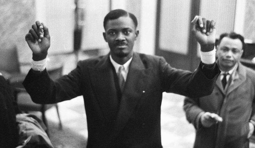 Photo: Lumumba raises his arms, injured by shackles, after his release from prison