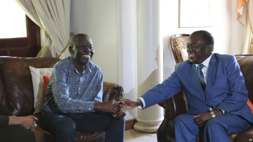 Zimbabwean President Emmerson Mnangagwa,right, chats to Morgan Tsvangirai, the main opposition leader in Zimbabwe during a visit to his residence in Harare, Friday, Jan, 5, 2018. Mnangagwa said Tsvangirai was recovering well to treatment(AP Photo/Tsvangirayi Mukwazhi)