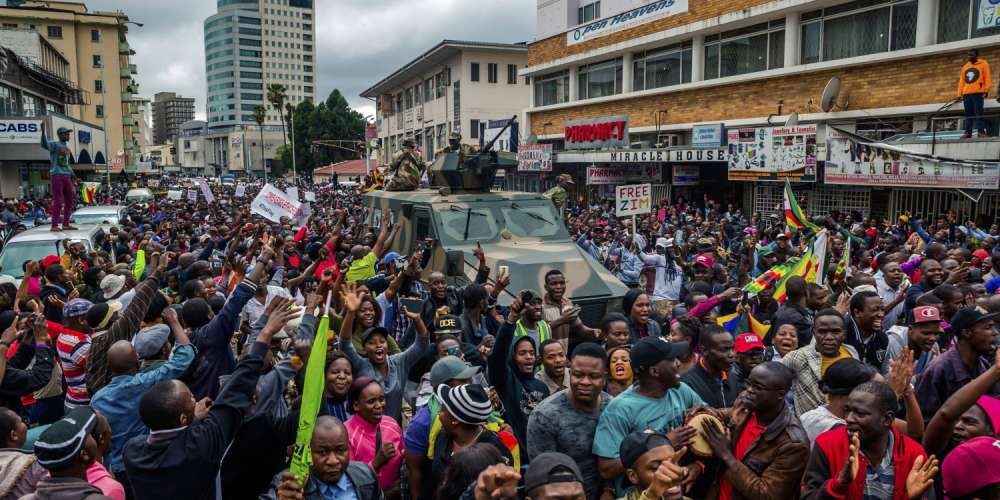 TOPSHOT - People cheer a passing Zimbabwe Defense Force military vehicle during a demonstration demanding the resignation of Zimbabwe's president on November 18, 2017 in Harare. Zimbabwe was set for more political turmoil November 18 with protests planned as veterans of the independence war, activists and ruling party leaders called publicly for Zimbabwe's President to be forced from office. / AFP PHOTO / Jekesai NJIKIZANA        (Photo credit should read JEKESAI NJIKIZANA/AFP/Getty Images)