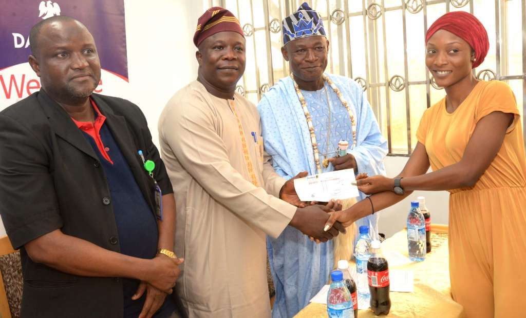 L-R: Human Assets Management & Admin, Dangote Cement Ibese, Abu Sufyan; Chairman Ewekoro North L.C.D.A, Hon. Kehinde Adepegba; His Royal Highness, Oba Kusoro Kayode, Olu Aga of Aga; and One of the scholarship beneficiary, Ayelotan Aminat, 300 Level student of University of Lagos at the presentation of scholarship award to the host communities of Dangote Cement, Ibese Plant, Ogun State, Friday, February 23, 2018