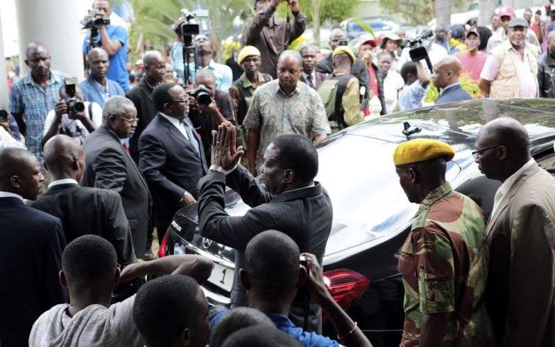 Zimbabwe President Emmerson Mnangagwa, center, leaves after paying his respects to the family of Morgan Tsvangirai, in Harare, Sunday, Feb. 18, 2018. Zimbabwe's veteran opposition leader Morgan Tsvangirai, aged 65, died Wednesday bringing an end to his long campaign to lead the country. Tsvangirai is set to be buried at his rural home in Buhera on Tuesday. (AP Photo/Tsvangirayi Mukwazhi)