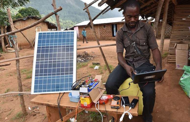 A man uses a solar energy panel to charge electric devices in Diebly, an Ivory Coast village without electricity. (Photo: Sia Kambou/AFP/Getty Images)