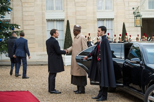French President Emmanuel Macron (L) greets Nigeria President Muhammadu Buhari upon his arrival at the Elysee palace on December 12, 2017 in Paris, for a lunch as part of the One Planet Summit. / AFP PHOTO / CHRISTOPHE ARCHAMBAULT
