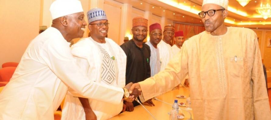 Shehu Garba receiving a hand shake from President Buhari