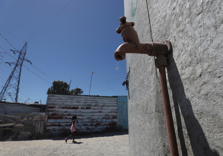 Residents walk past a leaking communal tap in Khayelitsha township, near Cape Town, South Africa, December 12, 2017. Picture taken December 12, 2017. REUTERS/Mike Hutchings