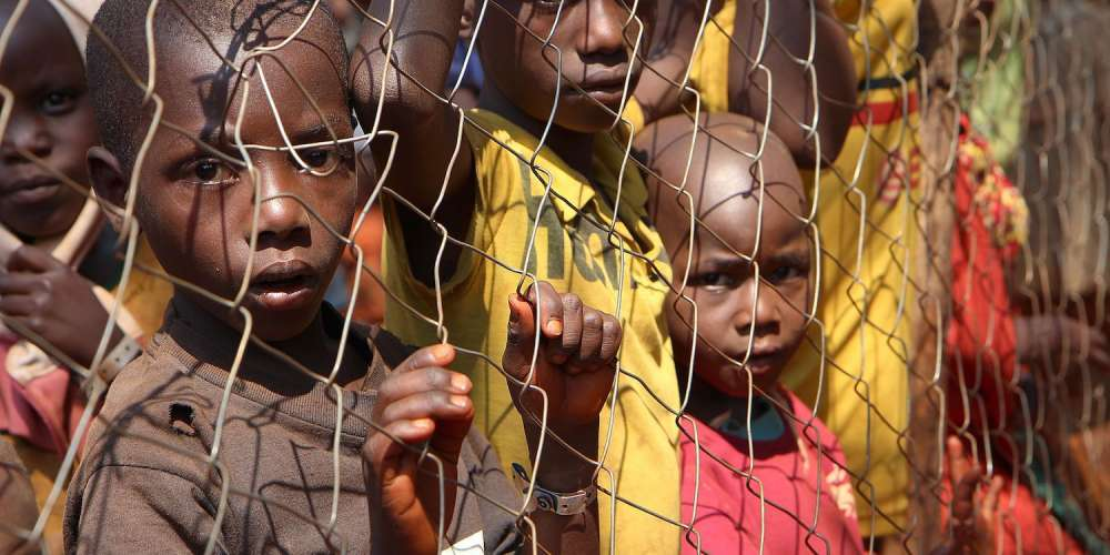 Burundian children, who fled their country, stand behind a fence as they wait to be registered as refugees at Nyarugusu camp, in north west of Tanzania, on June 11, 2015. Since early April, more than 100,000 people have fled to neighbouring countries -- mainly to Tanzania -- from Burundi due to political violence sparked by the country's president to seek a controversial third term. AFP PHOTO/STEPHANIE AGLIETTI        (Photo credit should read STEPHANIE AGLIETTI/AFP/Getty Images)