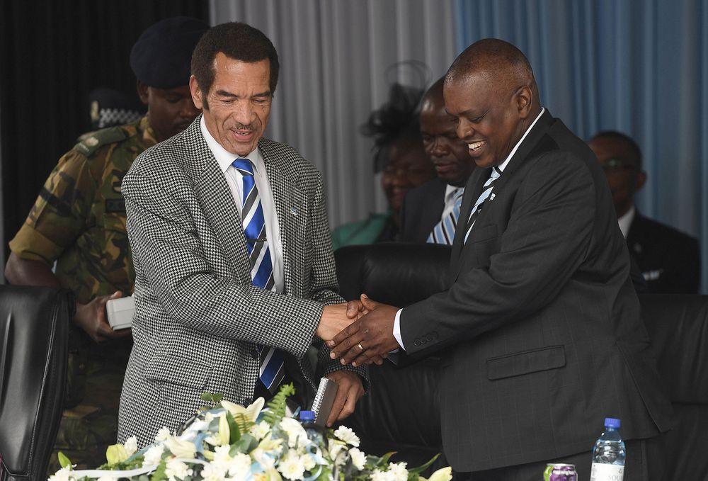 Ian Khama, left, shakes hands with Mokgweetsi Masisi. Phoographer: Monirul Bhuiyan/AFP/Getty Images