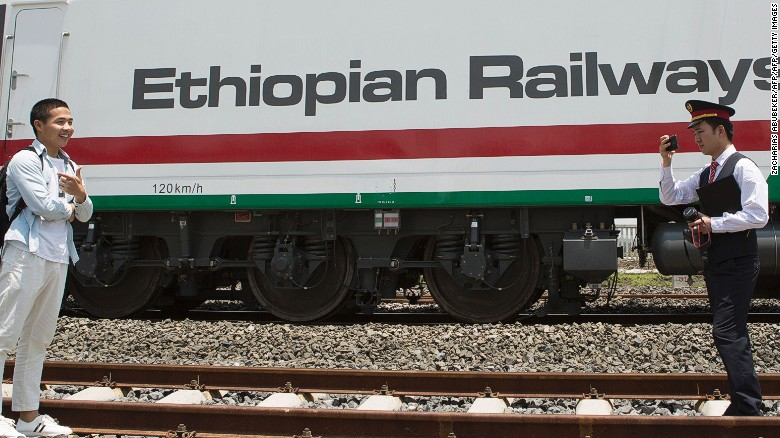Chinese employees of the new railway which will link Addis Ababa to Djibouti take pictures in front of the Chinese-made Ethiopian trains in Addis Ababa on September 24, 2016.