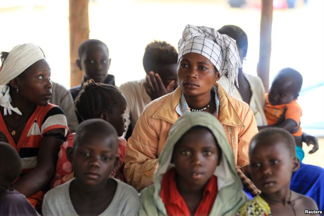 FILE - Mothers and children, refugees from from Democratic Republic of Congo, wait to be registered by UNHCR personnel, in Ntoroko, Uganda, Feb. 17, 2018.