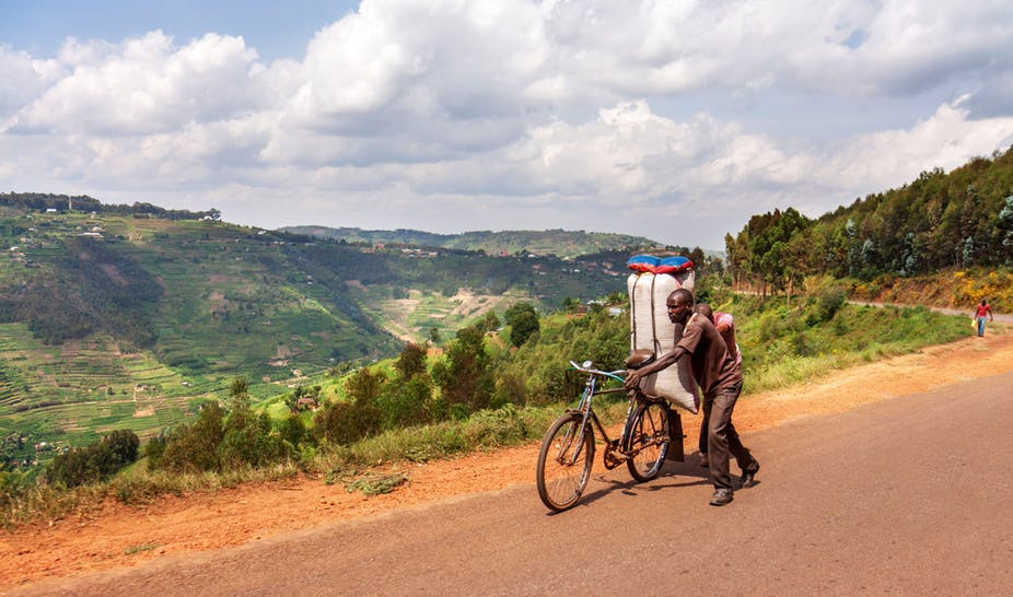 Men transporting a large bag in the Muvumba river valley in Kigali. A massive Rwandan electrification programme sets out to benefit rural communities. Shutterstock