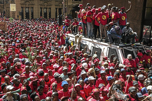 Demonstrators wearing a t-shirt of the National Union of Metalworkers of South Africa (Numsa) take part in a national strike called by South African Federation of Trade Unions SAFTU against a government proposed minimum wage on April 25, 2018 in Johannesburg. / AFP PHOTO / MUJAHID SAFODIEN