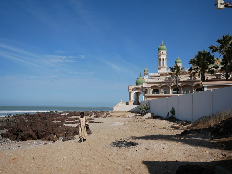 A man walks by the mosque in the coastal city of Gunjur on February 26, 2018. Environmentalists allege a Chinese plant there is polluting the sea.SOURCE ANNA PUJOL MAZZINI
