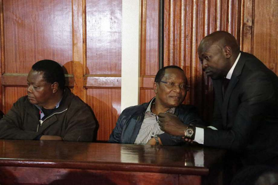 Lawyer Wycliff Ombatti, right speaks to NYS Richard Ndubai, as he appears with other suspects accused of corruption, at the Mililani law court in Nairobi, Kenya Tuesday, May 29, 2018. Kenyan authorities have charged 24 officials in what prosecutors call the first stage of investigations into a $79 million corruption scandal that has pressured President Uhuru Kenyatta to crack down on graft. less