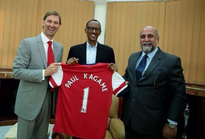 Kagame receiving an Arsenal jersey from Tony Adams (L) once Arsenal captain as Airtel MD, Teddy Bhullar, looks on