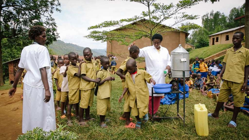 Children at Rwesero Primary School in Rwanda wash their hands before receiving treatment for intestinal worms and schistosomiasis during an END Fund supported mass drug administration.
