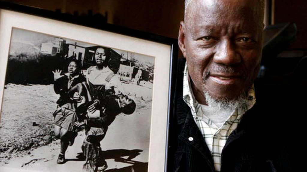 FILE - In this April 27, 2011 file photo, South African photographer Sam Nzima poses with his iconic photo showing 13-year-old Hector Pieterson being carried after being shot dead by apartheid police during the 1976 Soweto uprising, in Pretoria, South Africa. South Africa's state broadcaster, the South African Broadcasting Corporation, reported that Nzima, 83, died in the northwestern city of Nelspruit on the night of Saturday, May 12, 2018. Denis Farrell, File AP Photo
