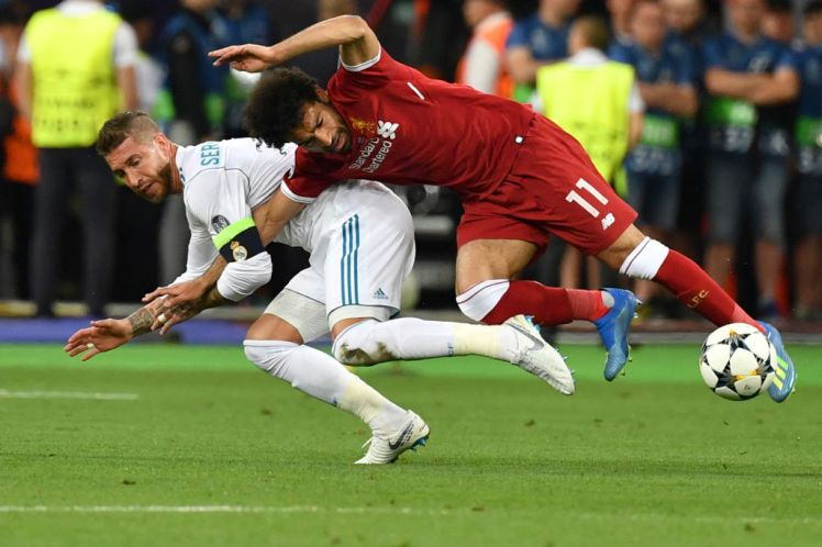 TOPSHOT - Liverpool's Egyptian forward Mohamed Salah (R) falls with Real Madrid's Spanish defender Sergio Ramos leading to Salah being injured during the UEFA Champions League final football match between Liverpool and Real Madrid at the Olympic Stadium in Kiev, Ukraine, on May 26, 2018. Picture  credit GENYA SAVILOV/AFP/Getty Images