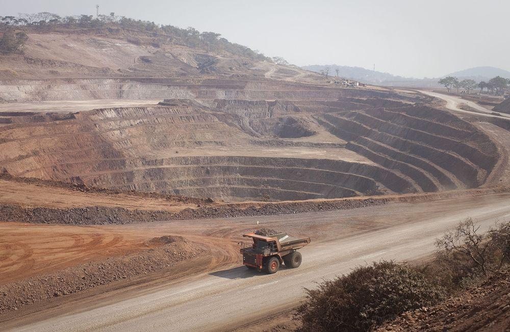 A Caterpillar Inc. mining truck drives past an open pit excavation at the Mutanda copper and cobalt mine in Mutanda, Katanga province. Photographer: Simon Dawson/Bloomberg