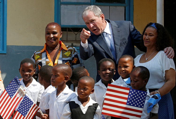 Former US President George W. Bush greets children at a school in Gaborone, Botswana