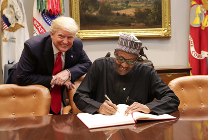 President Donald Trump of United States (l) pose while President Muhammadu Buhari signs visitors book at the White House in Washington DC during a recent visit