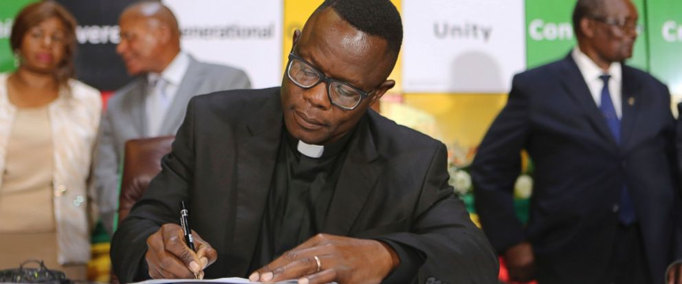 A pastor signs an agreement committing to a peaceful campaign ahead of historic elections in Harare, Zimbabwe, Tuesday, June, 26, 2018. Several Zimbabwean presidential candidates and political parties condemned the explosion over the weekend that narrowly missed Zimbabwe President Emmerson Mnangagwa and signed an agreement to have a peaceful campaign ahead of elections at the end of July. (AP Photo/Tsvangirayi Mukwazhi)
