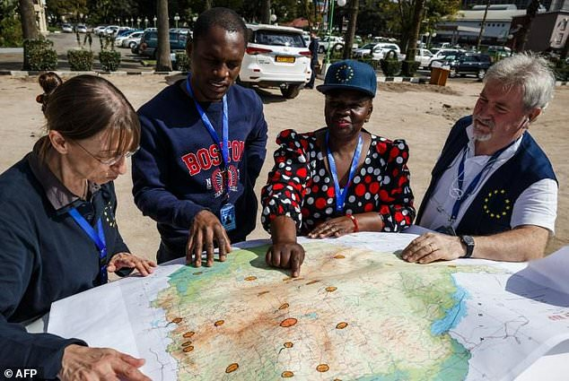 EU observers study a map upon arrival, as part of their deployment in the European Union Election Observation Mission