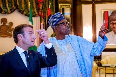 French President Emmanuel Macron speaks with Nigeria's President Muhammadu Buhari at the Presidential State House in Abuja, Nigeria, July 3, 2018. Nigeria Presidency/Handout via Reuters
