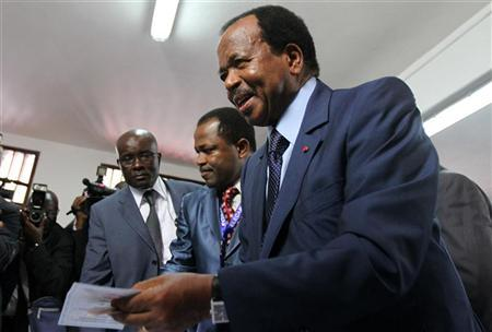 Cameroon's President Paul Biya holds a ballot paper before casting his vote at a polling centre in the capital Yaounde October 9, 2011. REUTERS/Akintunde Akinleye. In power for 36 years, the 85 old is seeking another term with the country facing unprecedented crisis