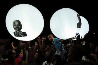 FILE PHOTO: A boy looks on in front of balloons bearing a picture of former South African President Nelson Mandela on Vilakazi Street in Soweto, South Africa, December 7, 2013. REUTERS/Siphiwe Sibeko/File FotoREUTERS