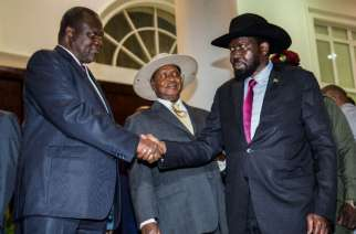 South Sudanese President Salva Kiir (R) shakes hands with opposition leader Riek Machar (L) during peace talks at Uganda's statehouse in Entebbe on July 7, 2018, ahead of their agreement to sign a preliminary power-sharing deal (AFP Photo/SUMY SADURNI)