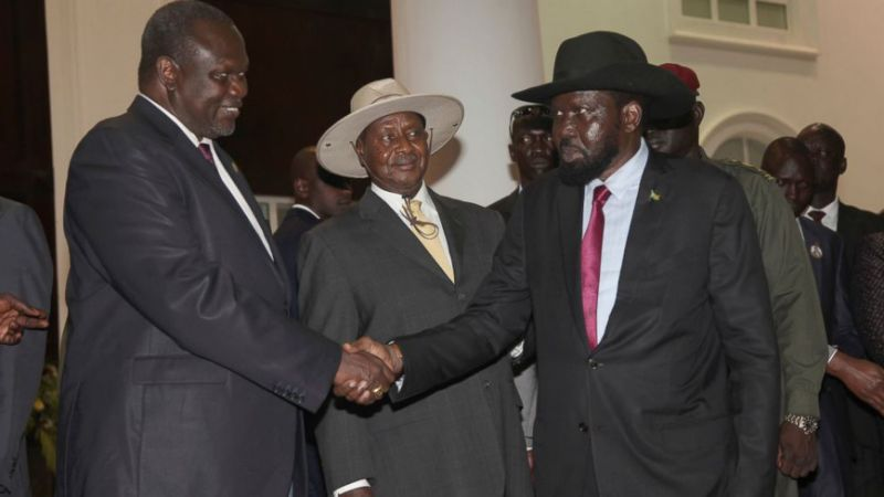 In this Saturday, July 7, 2018 photo, former Vice President of South Sudan Riek Machar, left, greets South Sudan President Salva Kiir as Uganda President Yoweri Museveni, center, looks on as they meet for a security meeting to find a lasting solution to insecurity in South Sudan, at the State House, in Entebbe, Uganda. (AP Photo/Stephen Wandera)